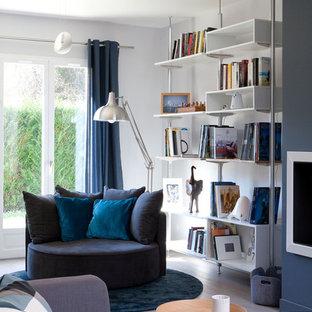 Cette image montre une salle de séjour avec une bibliothèque ou un coin lecture design de taille moyenne et ouverte avec un sol en bois clair, un mur blanc et un sol gris.