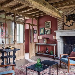 Exemple d'une salle de séjour nature fermée avec un mur rouge et une cheminée standard.