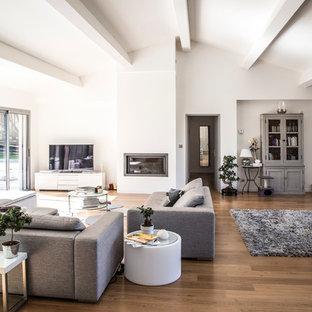 Idées déco pour une grande salle de séjour avec une bibliothèque ou un coin lecture contemporaine ouverte avec un mur blanc, un sol en bois brun, une cheminée ribbon et un téléviseur indépendant.