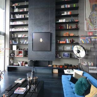 Cette image montre une salle de séjour avec une bibliothèque ou un coin lecture design de taille moyenne et ouverte avec un mur noir, une cheminée standard et aucun téléviseur.