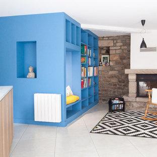 Cette photo montre une salle de séjour avec une bibliothèque ou un coin lecture éclectique ouverte et de taille moyenne avec un mur bleu, un sol en carrelage de céramique, une cheminée standard et un manteau de cheminée en pierre.