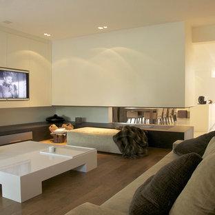 Idée de décoration pour une salle de séjour tradition de taille moyenne et ouverte avec un mur blanc, un sol en bois brun, une cheminée double-face et un téléviseur encastré.