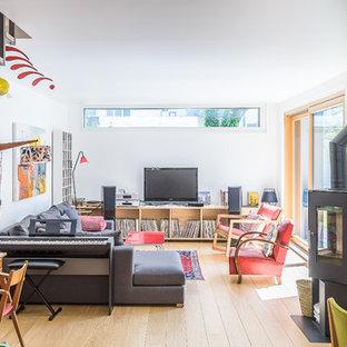 Exemple d'une salle de séjour tendance de taille moyenne et ouverte avec une salle de musique, un mur blanc, un sol en bois clair et un téléviseur indépendant.