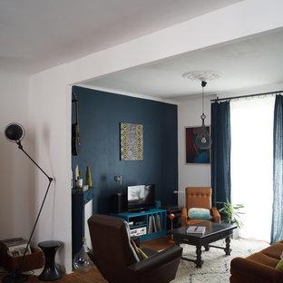Cette image montre une salle de séjour design de taille moyenne et ouverte avec un sol en bois brun, un téléviseur indépendant et un mur multicolore.