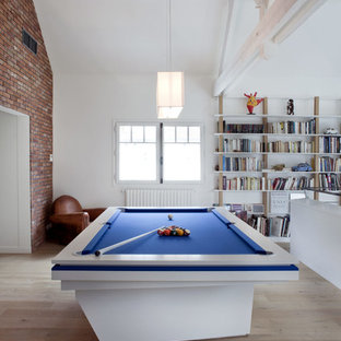 Inspiration for a large eclectic medium tone wood floor game room remodel in Paris with white walls and no tv