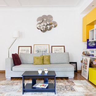 Réalisation d'une salle de séjour avec une bibliothèque ou un coin lecture design de taille moyenne et ouverte avec un mur blanc et un sol en bois brun.