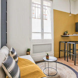パリの中サイズのインダストリアルスタイルのおしゃれなファミリールーム (黄色い壁、無垢フローリング、暖炉なし、壁掛け型テレビ、茶色い床、ライブラリー) の写真
