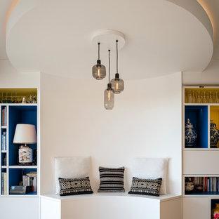 Exemple d'une grande salle de séjour avec une bibliothèque ou un coin lecture asiatique ouverte avec un mur blanc, un sol en bois brun, aucune cheminée et un téléviseur dissimulé.