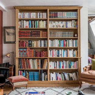 Inspiration pour une salle de séjour avec une bibliothèque ou un coin lecture méditerranéenne avec un mur blanc, un sol en bois brun, un téléviseur indépendant et un sol marron.