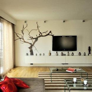 Idée de décoration pour une salle de séjour design de taille moyenne et fermée avec un mur blanc, un sol en bois clair, aucune cheminée et un téléviseur fixé au mur.