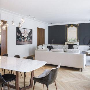 Aménagement d'une grande salle de séjour contemporaine ouverte avec un sol en bois clair, une cheminée standard, un manteau de cheminée en pierre, un mur blanc et un téléviseur dissimulé.