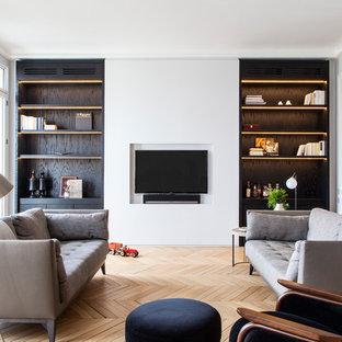 Idée de décoration pour une grande salle de séjour design ouverte avec un mur blanc, un sol en bois clair, un téléviseur encastré et un sol marron.