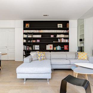Idée de décoration pour une grande salle de séjour avec une bibliothèque ou un coin lecture nordique ouverte avec un mur blanc, un sol en bois clair, aucune cheminée, un téléviseur indépendant et un sol beige.