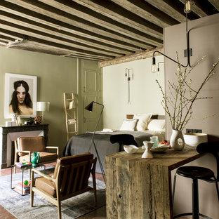 Esempio di un piccolo soggiorno bohémian aperto con pareti grigie, pavimento in terracotta, nessuna TV, pavimento rosso, camino classico e cornice del camino in cemento