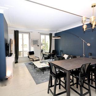 パリの大きいコンテンポラリースタイルのおしゃれなファミリールーム (青い壁、コンクリートの床、標準型暖炉、漆喰の暖炉まわり、壁掛け型テレビ、ベージュの床) の写真