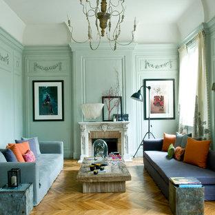 Idée de décoration pour une grande salle de séjour bohème fermée avec un mur bleu, un sol en bois brun, aucun téléviseur, une cheminée standard, un manteau de cheminée en pierre et un sol beige.