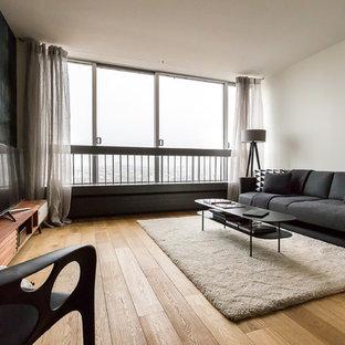 Idée de décoration pour une salle de séjour design de taille moyenne et ouverte avec un sol en bois clair, un mur noir, un téléviseur indépendant et aucune cheminée.