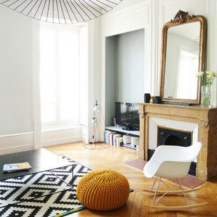 リヨンの大きいエクレクティックスタイルのおしゃれなファミリールーム (白い壁、無垢フローリング、標準型暖炉、石材の暖炉まわり、据え置き型テレビ) の写真