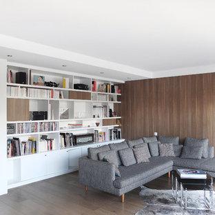 Cette photo montre une salle de séjour avec une bibliothèque ou un coin lecture tendance de taille moyenne et ouverte avec un mur blanc, un sol en bois clair, aucune cheminée et aucun téléviseur.