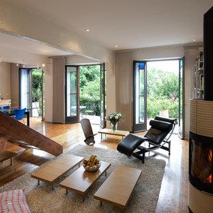 Idée de décoration pour une grande salle de séjour design ouverte avec un mur blanc, un sol en bois brun et aucun téléviseur.