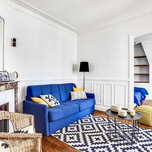 Idée de décoration pour une salle de séjour bohème fermée avec un mur blanc, un sol en bois brun, une cheminée standard, un manteau de cheminée en plâtre et un sol marron.