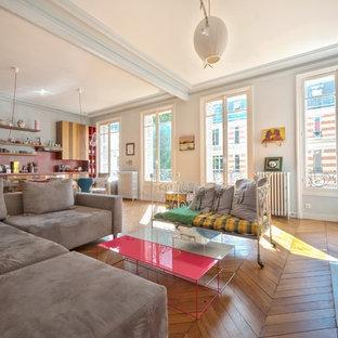 Idée de décoration pour une grande salle de séjour bohème ouverte avec un mur bleu, un sol en bois brun, une cheminée standard, un manteau de cheminée en pierre et aucun téléviseur.