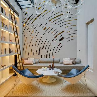 Cette image montre une salle de séjour avec une bibliothèque ou un coin lecture design de taille moyenne avec un mur blanc, un sol en bois clair et aucun téléviseur.