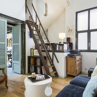 Réalisation d'une salle de séjour avec une bibliothèque ou un coin lecture urbaine avec un mur blanc, un sol en bois clair et aucune cheminée.