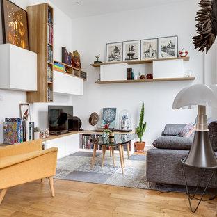 Cette image montre une salle de séjour avec une bibliothèque ou un coin lecture bohème fermée avec un mur blanc, un sol en bois brun, un téléviseur indépendant et un sol marron.