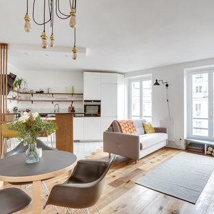 Idées déco pour une salle de séjour scandinave ouverte avec un mur blanc, un sol en bois brun, une cheminée standard, un téléviseur indépendant et un sol marron.
