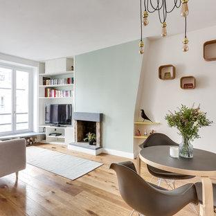 Inspiration pour une salle de séjour nordique ouverte avec un mur blanc, un sol en bois brun, une cheminée standard, un téléviseur indépendant et un sol marron.
