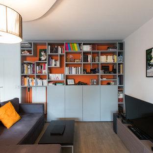 Foto di un grande soggiorno minimal aperto con libreria, pareti arancioni, parquet chiaro, TV autoportante e nessun camino