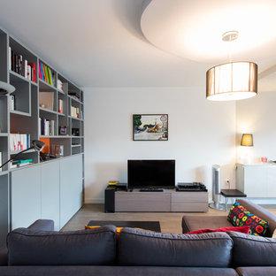 Exemple d'une grand salle de séjour avec une bibliothèque ou un coin lecture tendance ouverte avec un mur blanc, un sol en bois clair et un téléviseur indépendant.