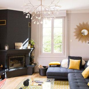 Aménagement d'une salle de séjour classique avec un mur beige, un sol en bois clair, une cheminée d'angle, un manteau de cheminée en pierre et un sol beige.