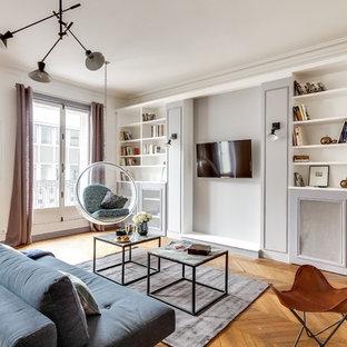 Cette image montre une salle de séjour avec une bibliothèque ou un coin lecture traditionnelle de taille moyenne et ouverte avec un mur gris, un sol en bois brun, un téléviseur fixé au mur et aucune cheminée.
