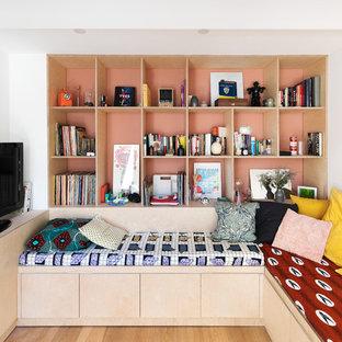 Aménagement d'une salle de séjour avec une bibliothèque ou un coin lecture contemporaine ouverte avec un sol en bois clair, un mur blanc, aucune cheminée, un téléviseur indépendant et un sol marron.
