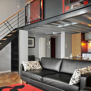 Réalisation d'une salle de séjour design de taille moyenne avec un mur gris et un sol en bois brun.