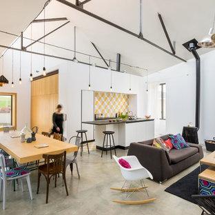 Aménagement d'une salle de séjour éclectique de taille moyenne et ouverte avec un mur blanc, béton au sol et aucun téléviseur.