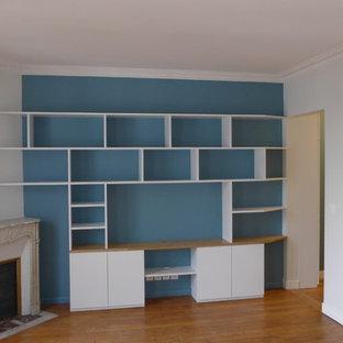 パリの広い北欧スタイルのおしゃれな独立型ファミリールーム (ライブラリー、青い壁、淡色無垢フローリング、コーナー設置型暖炉、石材の暖炉まわり、壁掛け型テレビ) の写真