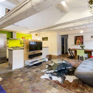 Cette photo montre une salle de séjour éclectique ouverte et de taille moyenne avec un mur blanc, un téléviseur fixé au mur, un sol en carreau de terre cuite et aucune cheminée.