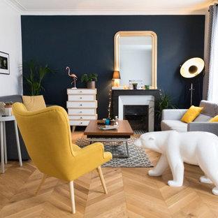 パリの中くらいのミッドセンチュリースタイルのおしゃれな独立型ファミリールーム (青い壁、淡色無垢フローリング、標準型暖炉、石材の暖炉まわり、据え置き型テレビ、茶色い床) の写真