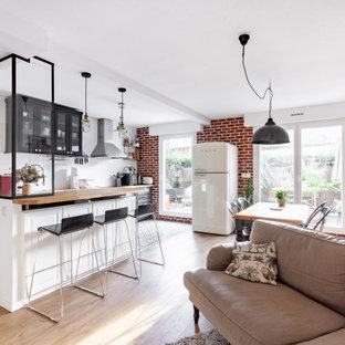Cette image montre une salle de séjour traditionnelle de taille moyenne et ouverte avec un mur blanc, un sol en bois clair et un sol beige.