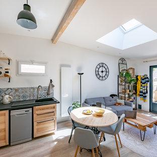 Cette image montre une salle de séjour méditerranéenne de taille moyenne et ouverte avec un mur blanc, un sol en bois clair, un sol beige et un téléviseur indépendant.
