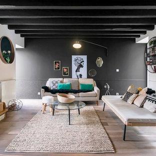 他の地域の大きいエクレクティックスタイルのおしゃれなファミリールーム (黒い壁、淡色無垢フローリング、据え置き型テレビ、暖炉なし) の写真