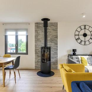 Imagen de sala de estar abierta, contemporánea, de tamaño medio, con paredes blancas, suelo laminado, estufa de leña, marco de chimenea de metal y suelo beige