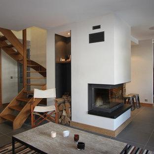 Idée de décoration pour une grande salle de séjour chalet ouverte avec un mur blanc et un sol en ardoise.