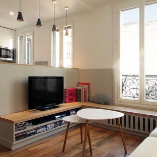 This is an example of a small scandi open plan family and games room in Paris with light hardwood flooring, no fireplace, a wall mounted tv and multi-coloured walls.