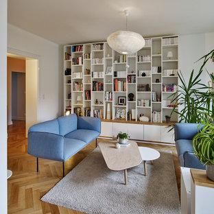 Cette image montre une grand salle de séjour avec une bibliothèque ou un coin lecture nordique ouverte avec un mur blanc, un sol en bois clair et un sol beige.