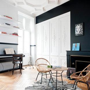 Réalisation d'une grande salle de séjour design avec un mur noir, un sol en bois brun, une salle de musique, une cheminée standard et aucun téléviseur.