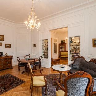 トゥールーズの大きいヴィクトリアン調のおしゃれなファミリールーム (白い壁、淡色無垢フローリング、標準型暖炉、木材の暖炉まわり、テレビなし) の写真